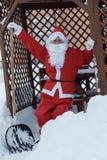 在铁锹的骄傲的圣诞老人倾斜在积雪的清除以后工作在f的 免版税图库摄影