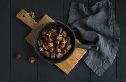 在铁长柄浅锅平底锅的烤栗子在土气木板 图库摄影