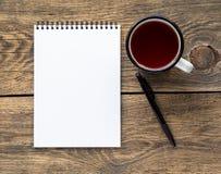 在铅笔和一个杯子茶附近打开在春天的笔记本有笔记的白皮书的和图画 免版税库存照片