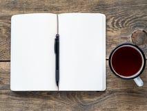 在铅笔和一杯茶附近打开在春天的笔记本有笔记的白皮书的和图画 免版税库存照片