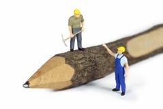 在铅笔顶部的微型建筑工人 图库摄影