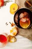 在铜平底深锅的被仔细考虑的酒烹调了与切片桔子、苹果和麝香草 图库摄影