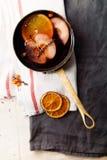 在铜平底深锅的被仔细考虑的酒烹调了与切片桔子、苹果和麝香草 免版税库存照片