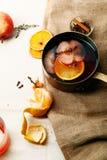 在铜平底深锅的被仔细考虑的酒烹调了与切片桔子、苹果和麝香草 免版税库存图片