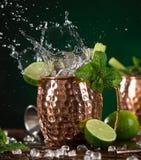 在铜杯子的著名飞溅的莫斯科骡子酒精鸡尾酒 免版税库存图片