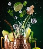 在铜杯子的著名飞溅的莫斯科骡子酒精鸡尾酒 库存图片