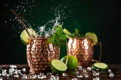 在铜杯子的著名飞溅的莫斯科骡子酒精鸡尾酒 免版税库存照片