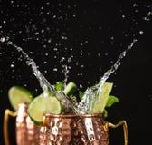 在铜杯子的著名飞溅的莫斯科骡子酒精鸡尾酒 库存照片