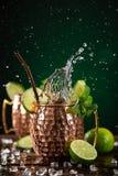 在铜杯子的著名飞溅的莫斯科骡子酒精鸡尾酒 图库摄影