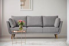 在铜桌上的花在明亮的客厅内部的灰色沙发前面与海报 实际照片 免版税库存照片