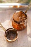 在铜罐的咖啡准备有室外热的金黄的沙子的 免版税库存图片