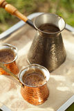 在铜罐的咖啡准备有室外热的金黄的沙子的 图库摄影