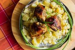 在铝圆的盘的开胃被烘烤的土豆与炸鸡和葱和酱瓜和大蒜 免版税库存照片