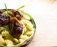 在铝圆的盘的开胃被烘烤的土豆与炸鸡和葱和酱瓜和大蒜 库存图片