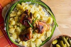 在铝圆的盘的开胃被烘烤的土豆与炸鸡和葱和酱瓜 库存图片