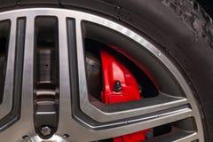 在铝轮子的零件的特写镜头通过一个穿孔的闸圆盘和跑车红色支持是的轮幅 免版税图库摄影