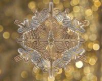 在银的冬天雪花在金黄背景 图库摄影
