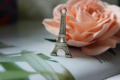 在银的微型埃佛尔铁塔在一朵开花的桃红色玫瑰的背景 库存图片