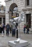 在银绘的街道艺术家执行物理魔术在科文特花园,伦敦,英国 库存照片