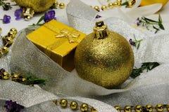 在银色丝带和圣诞节玩具覆盖的一个金黄礼物盒 库存图片