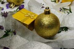 在银色丝带和圣诞节玩具覆盖的一个金黄礼物盒 免版税图库摄影
