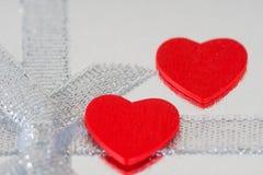 在银色丝带的两红色心脏 免版税图库摄影
