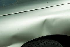 在银色汽车一边的消弱的金属板在停车场的事故损坏了 免版税库存照片