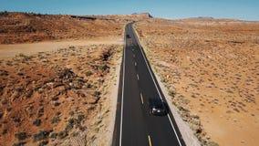 在银色汽车之后的寄生虫在空的沙漠高速公路路在亚利桑那,照相机掀动显露平的风景和地平线 股票视频