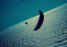在银色海的一个孤立滑翔伞有黑暗的云彩的晚上 免版税库存照片