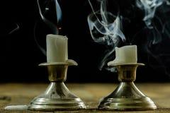 在银色烛台的盛开的蜡烛有熏制的灯芯的 烟为 库存照片