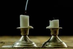 在银色烛台的盛开的蜡烛有熏制的灯芯的 烟为 免版税图库摄影