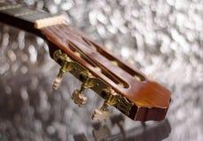 在银色背景的吉他床头柜 免版税库存照片
