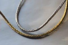 在银色背景的银和金麻线 库存图片