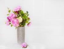 在银色花瓶的桃红色花在白色墙壁背景 免版税库存图片