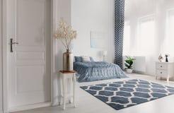 在银色花瓶的花在绝密旁边的木桌上对有被仿造的地毯和白色fu的典雅的纽约样式卧室 免版税库存图片