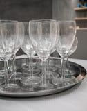 在银色金属盘子的酒杯在白色桌上 免版税图库摄影