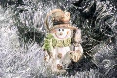 在银色闪亮金属片中的被雕刻的古板的雪人 免版税库存图片