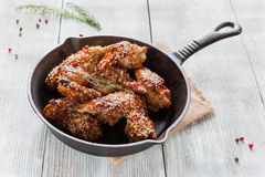 在铸铁平底锅的鸡翼在木桌上 用卤汁泡在蕃茄和蜂蜜调味汁 烘烤与芝麻籽 图库摄影