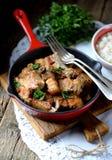 在铸铁煎锅的油煎的猪肚用葱、大蒜和酱油 库存照片
