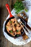 在铸铁煎锅的油煎的猪肚用葱、大蒜和酱油 库存图片
