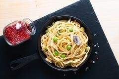 在铸铁长柄浅锅平底锅的食物概念自创意粉乳白色调味汁在板岩石头 库存照片