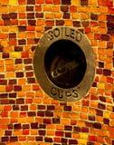 在铺磁砖的墙壁的被弄脏的杯子垃圾容器 文本 免版税库存照片