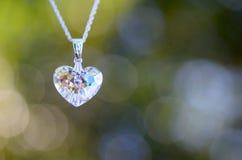 在链子的水晶心脏有Bokeh背景 免版税图库摄影