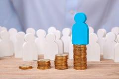 在销售和赢利的成长 工作者人群和堆在领导顶部的硬币台阶 库存照片