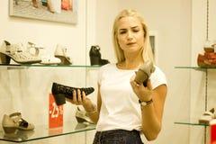 在销售期间,一名愉快的白肤金发的妇女购物并且选择夏天鞋子 ES, 免版税库存图片