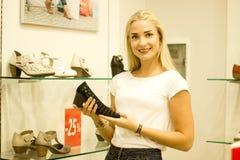在销售期间,一名愉快的白肤金发的妇女购物并且选择夏天鞋子 ES, 库存照片