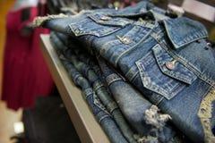 在销售机架的蓝色牛仔布背心 免版税图库摄影
