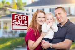 在销售标志的和议院前面的年轻军事家庭 免版税库存图片
