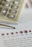 在销售额图表的计算器和圆珠笔 免版税库存图片