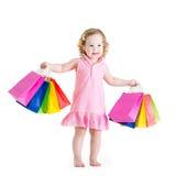 在销售以后的美丽的小女孩带着她五颜六色的包 免版税库存照片